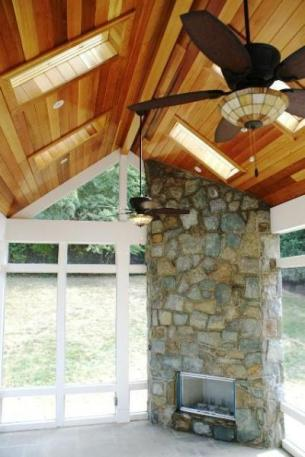 Montgomery County, MD, cedar ceiling porch with stunning outdoor fireplace integration.